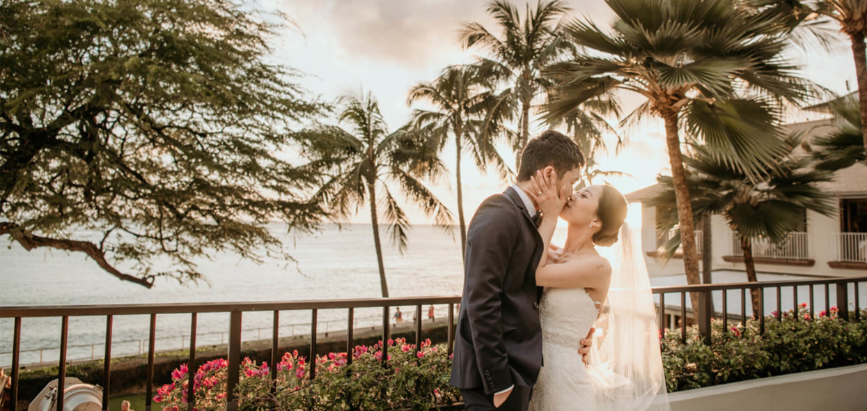 Wedding couple share a kiss at sunset