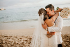 Wedding couple embrace on the beach