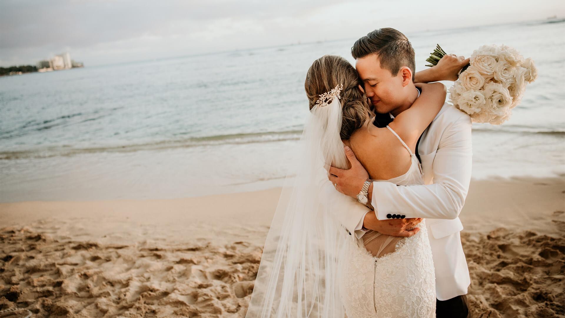 Wedding couple embrace on the beach